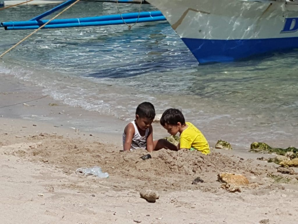 Our son playing on the beach with another kid in the Philippines